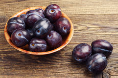 Ripe plums. In bowl and near on old wooden table Stock Images