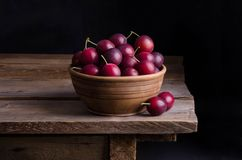 Ripe plums in the bowl on wooden table. Ripe plums in the ceramic bowl on wooden table Stock Photography