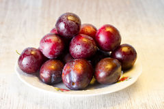 Ripe plums and cherry-plum on a table Stock Images