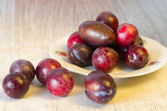 Ripe plums and cherry-plum on a table Royalty Free Stock Images