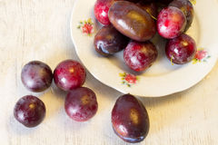 Ripe plums and cherry-plum on a table Royalty Free Stock Photo
