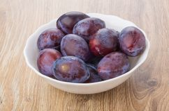 Ripe plums in glass white bowl on table. Ripe plums in glass white bowl on wooden table Royalty Free Stock Photo
