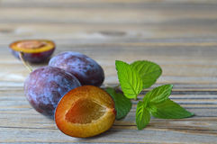 Ripe plums and mint leaves Royalty Free Stock Photos