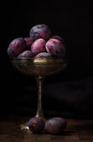 Ripe plums in a old silver cup in dark food photography style Stock Photography