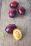 Ripe plums on old wood table Stock Photography