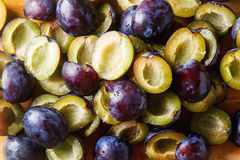 Ripe plums scattered on a brown wooden background. Bio healthy f. Ruits. Selective focus Royalty Free Stock Photography