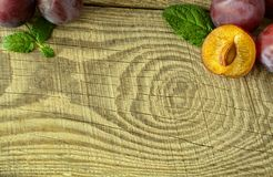 Ripe plums on a textured wooden board. Large ripe autumn plums, located in the corner of a textured wooden board, with a place for inscription Royalty Free Stock Photos