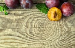 Ripe plums on a textured wooden board. Large ripe autumn plums, located in the corner of a textured wooden board, with a place for inscription Stock Photos