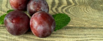Ripe plums on a textured wooden board. Large ripe autumn plums, located in the corner of a textured wooden board, with a place for inscription Stock Images