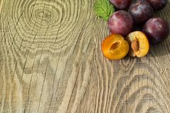 Ripe plums on a textured wooden board. Large ripe autumn plums, located in the corner of a textured wooden board, with a place for inscription Royalty Free Stock Image