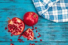 Ripe pomegranate and blue checkered towel wooden background Royalty Free Stock Photography
