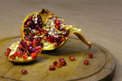 Ripe pomegranate is on the board. In the kitchen Royalty Free Stock Image