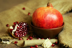 Ripe pomegranate in a bowl with seeds Royalty Free Stock Image