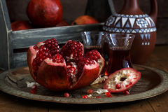 Ripe pomegranate on copper plate on a dark background, close view Royalty Free Stock Images