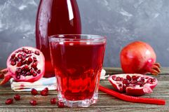 Ripe pomegranate fruit, bottle and glass of fresh pomegranate juice on wooden table. royalty free stock images