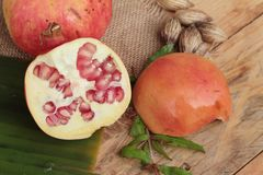 Ripe pomegranate fruit delicious on wood background. Stock Photo
