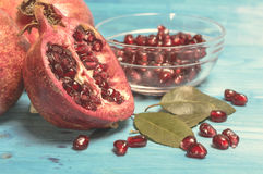 Ripe pomegranate fruit with juice on blue paint wooden vintage background. Stock Image