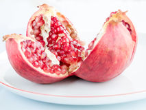 Ripe pomegranate fruit on a white porcelain plate Royalty Free Stock Photography