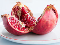 Ripe pomegranate fruit on a white porcelain plate Stock Images