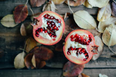 Ripe pomegranate fruit on wooden vintage background. Red juice p Stock Photos