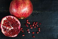 Ripe pomegranate, pomegranate kernels on black wooden background. stock images