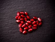 Ripe pomegranate seeds in form of heart on black slate background Stock Photos