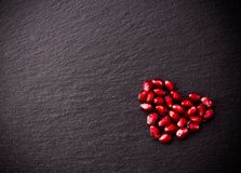 Ripe pomegranate seeds in form of heart on black slate background Royalty Free Stock Images