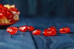 Ripe pomegranate slice and red garnet fruit seeds on table. Sele Royalty Free Stock Images