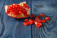 Ripe pomegranate slice and red garnet fruit seeds on table. Sele Royalty Free Stock Photography
