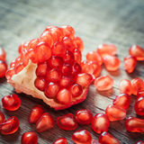 Ripe pomegranate slice and red garnet fruit seeds Stock Photo