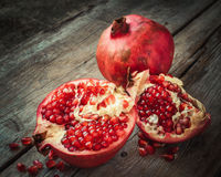 Ripe pomegranate slice and whole red garnet fruit on table. Stock Images