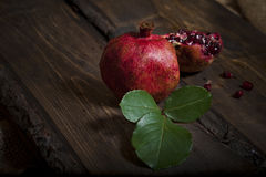 Ripe pomegranate. With a sprig stock photography