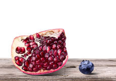 Ripe pomegranate and tasty blueberrie fruit on a table Stock Photography