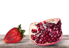 Ripe pomegranate and tasty strawberry fruit on a table Royalty Free Stock Image