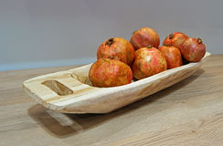 Ripe pomegranate in a wooden platter. Ripe pomegranates in the brutal wooden dish on a wooden table top Stock Images