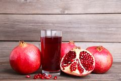 Ripe pomegranates and glass of juice on grey background royalty free stock photos