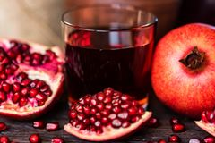 Ripe pomegranates with glass of juice on table. Close up ripe pomegranates with juice on wooden table Royalty Free Stock Image