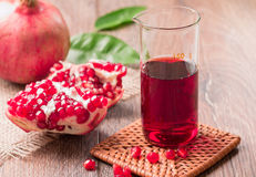 Ripe pomegranates with juice on table close-up royalty free stock image