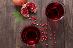 Ripe pomegranates with juice on wooden background royalty free stock photos
