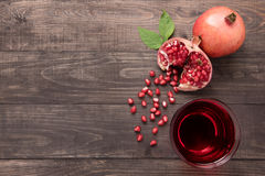 Ripe pomegranates with juice on wooden background stock images