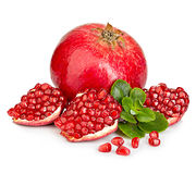 Ripe pomegranates with leaves close-up on a white background. Stock Photos