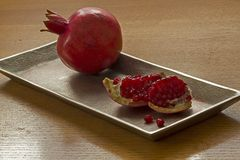 Ripe Pomegranates on metal decorated  plate Royalty Free Stock Photos