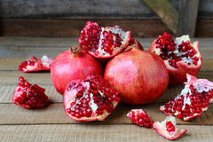 Ripe Pomegranates On A Rustic Table Stock Photo