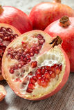 Ripe pomegranates on a wooden table. Some ripe pomegranates on a wooden table with seeds scattered Royalty Free Stock Image