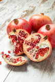 Ripe pomegranates on a wooden table. Some ripe pomegranates on a wooden table with seeds scattered Stock Images