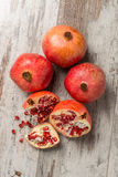 Ripe pomegranates on a wooden table. Some ripe pomegranates on a wooden table with seeds scattered Stock Photo
