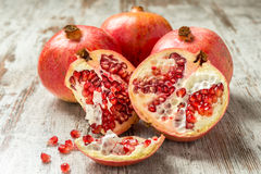 Ripe pomegranates on a wooden table. Some ripe pomegranates on a wooden table with seeds scattered Stock Image