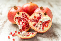 Ripe pomegranates on a wooden table. Some ripe pomegranates on a wooden table with seeds scattered Stock Photography