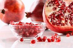 Ripe pomergranates and glass bowl of seeds Stock Photography