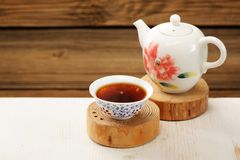 Ripe puerh tea in white bowl brewed in white porcelain pot Stock Photo